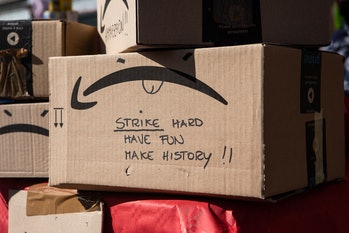 An Amazon box with the smile logo turned upside down is seen at a protest.