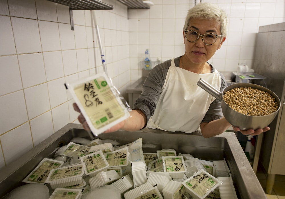 Japanese cook Chisa Ogawa, poses with packaged Tofu and soy beans ready to be processed, at her Suzu Tofu laboratory in Le Mans, northwestern France, on March 15, 2021. - In 2015, Japanese cook Chisa Ogawa took over from Mr. Suzuki, who produced Tofu in his garage in the Paris region for Japanese restaurants in the capital. Since then, she has moved the production to a laboratory in Le Mans, adapted the ancestral Japanese recipe to a Made in France soybean produced in the South West, and transformed 1.5 tonnes of soy per year into a full-fledged dish intended for starred chefs, or as accompaniment of meat or fish. (Photo by JEAN-FRANCOIS MONIER / AFP) (Photo by JEAN-FRANCOIS MONIER/AFP via Getty Images)