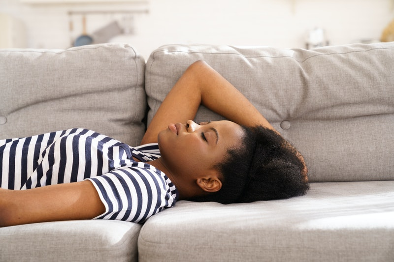 A woman in a striped shirt lies on a couch. These are signs your fatigue might be anxiety-related.