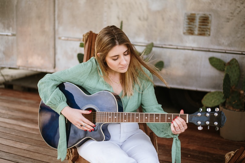 A young woman playing a guitar in a porch of a motor home