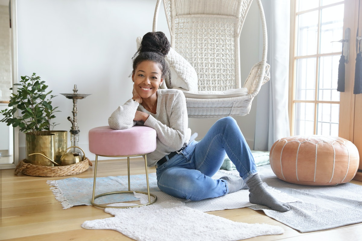 A woman lounges out on the floor at home and leans against a pink stool.