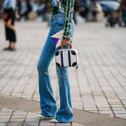 PARIS, FRANCE - OCTOBER 01: A guest wears blue flare denim pants, a black and white bag, outside Lou...