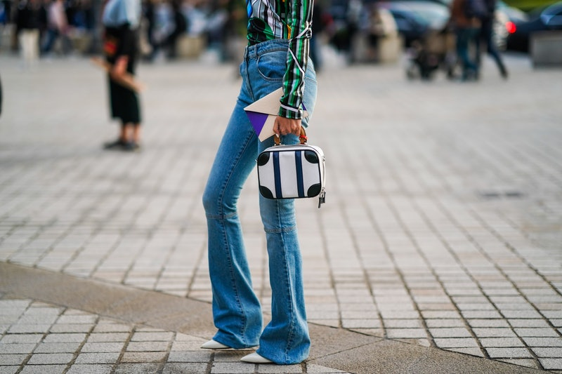 PARIS, FRANCE - OCTOBER 01: A guest wears blue flare denim pants, a black and white bag, outside Louis Vuitton, during Paris Fashion Week - Womenswear Spring Summer 2020, on October 01, 2019 in Paris, France. (Photo by Edward Berthelot/Getty Images)
