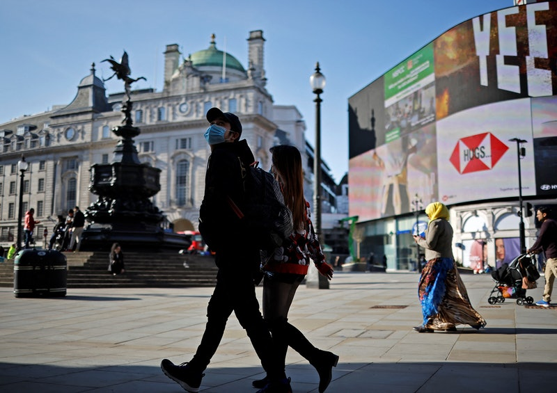 """A pedestrian wearing a face covering due to Covid-19 through an almost deserted Piccadilly Circus in central London on March 22, 2021. - Britain will on March 23, 2021, mark the one-year anniversary of the first coronavirus lockdown with a """"National Day of Reflection"""", which will see parliament hold a minute's silence in tribute to the more than 125,000 people who have died. (Photo by Tolga Akmen / AFP) (Photo by TOLGA AKMEN/AFP via Getty Images)"""