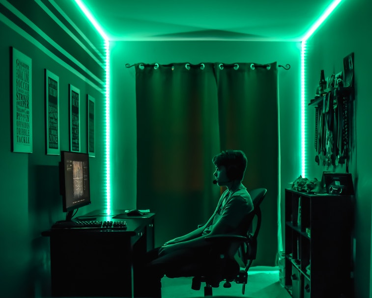 Man playing games on a PC in a darkly lit room.