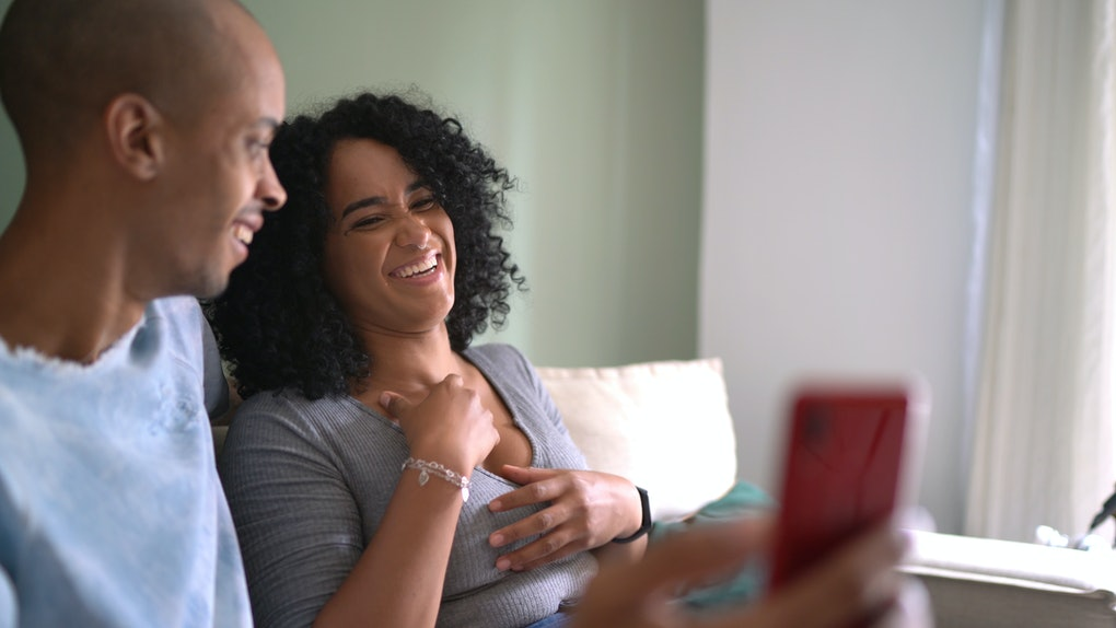 A happy couple laughs while recording a video on their phone.
