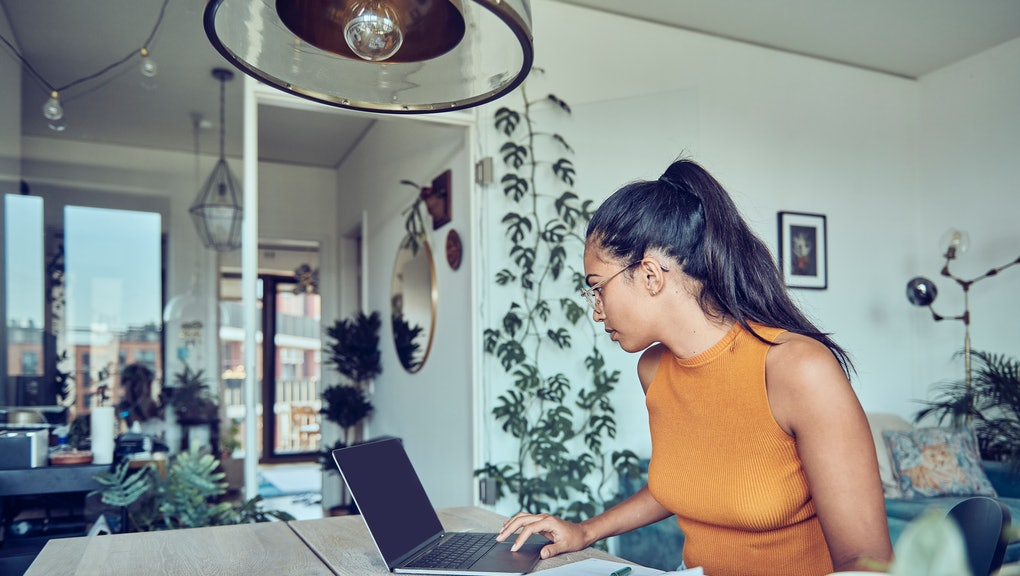 A woman is sitting at a dining table with a laptop and financial statements. Calculates and pays taxes and bills online.