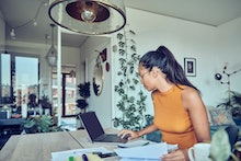 A woman is sitting at a dining table with a laptop and financial statements. Calculates and pays tax...