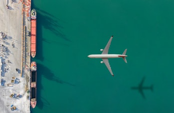 Airplane flying above commercial dock.