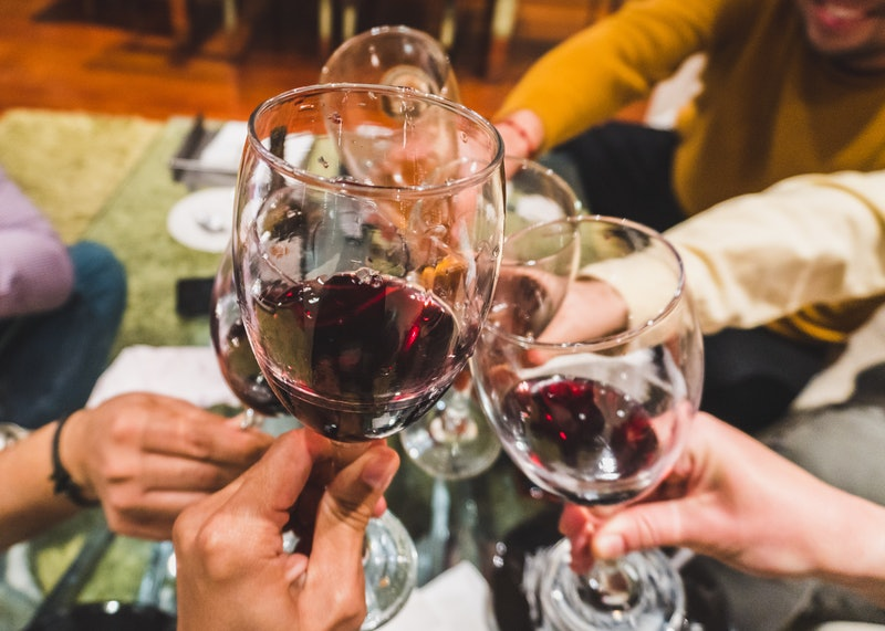 Friends toasting drinks at party. Focus on wineglasses