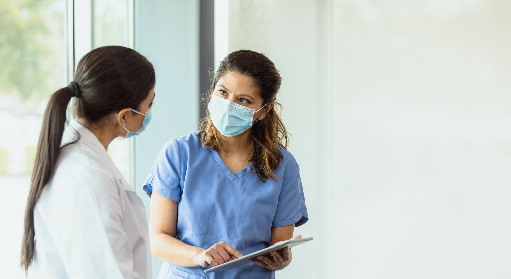 A female healthcare professional discusses a patient's case with a female colleague. She is pointing...