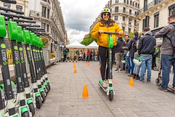 A rider is seen on an e-scooter, passing by a row of Lime scooters.