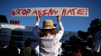 TOPSHOT - Sally Sha holds up a sign during a Stop Asian Hate rally at Discovery Green in downtown Ho...