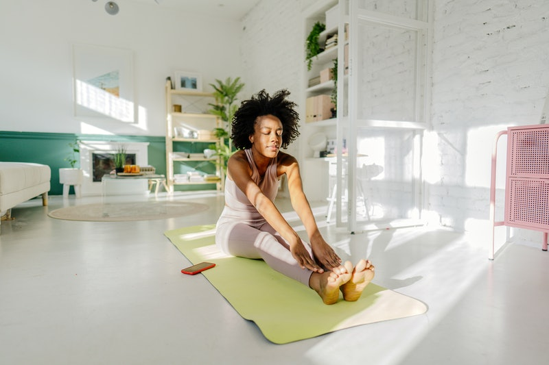 Photo of a young woman practicing yoga in the living room of her apartment; the daily routine of a young woman