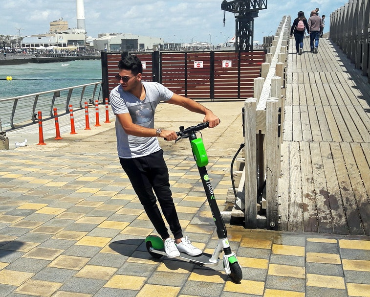 "Young man riding a LIME electric scooter in the new Promenade of Tel Aviv. Due to good weather and sun most of the year, Electric scooters are making their way in Tel Aviv.  ""Lime.S"" has more that 500 electric scooters that users can pick up and leave on city streets, without having to lock them up. The scooters are accessed by smartphones, and paid for by credit cards kept on file."