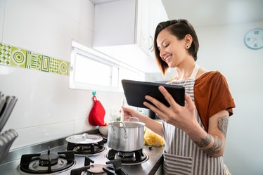 A woman cooks some soup in a pot, while looking at a recipe on her phone.
