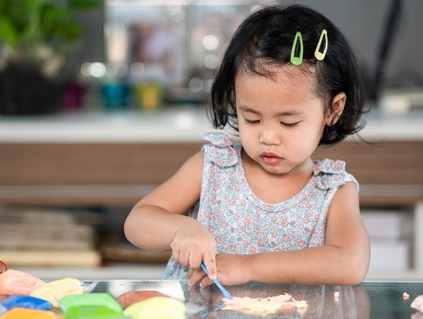 little girl playing with play-doh