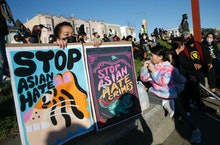 OAKLAND, CA - MARCH 23: Annie Hong, of Oakland, holds signs during an anti-Asian hate vigil at China...