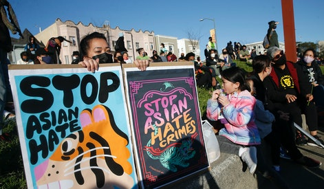 OAKLAND, CA - MARCH 23: Annie Hong, of Oakland, holds signs during an anti-Asian hate vigil at Chinatown's Madison Park in downtown Oakland, Calif., on Tuesday, March 23, 2021. Today marks the one-week anniversary of the murder of eight people at Atlanta spas, 6 of whom were Asian women. (Jane Tyska/Digital First Media/East Bay Times via Getty Images)