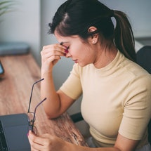 A woman deals with a headache linked to stress and anxiety.