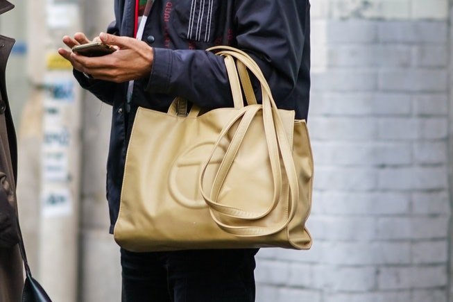 PARIS, FRANCE - OCTOBER 01: A guest wears a beige leather Telfar logo bag, during Paris Fashion Week - Womenswear Spring Summer 2021, on October 01, 2020 in Paris, France. (Photo by Edward Berthelot/Getty Images)