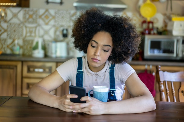 Depressed young afro woman texting on phone alone, sitting sad in the kitchen in her home