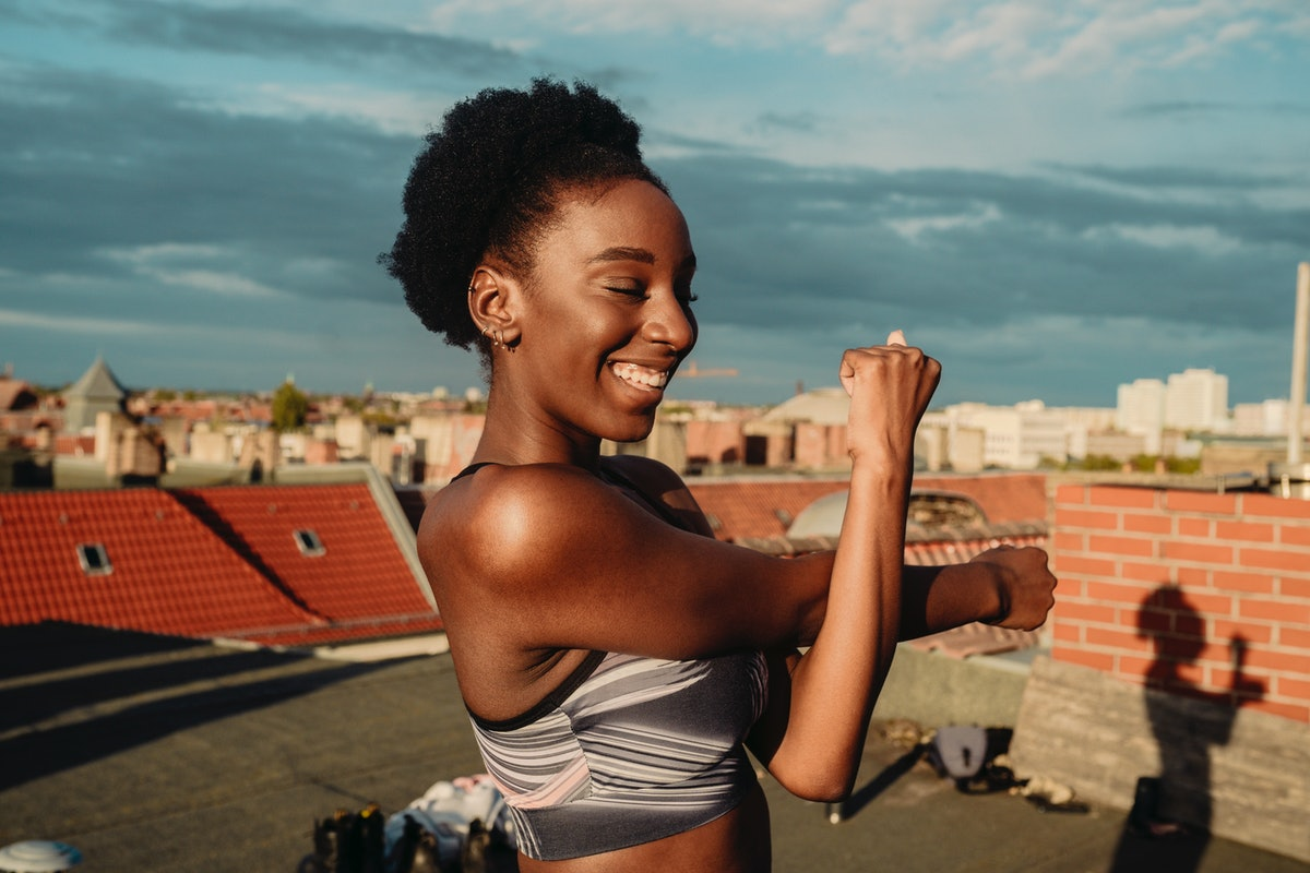 A young woman stretches before doing a sun salutation on the rooftop of her apartment building.