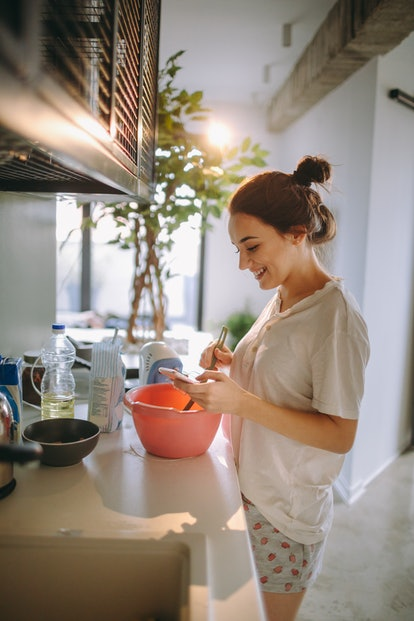 A young woman makes pancakes in her kitchen while watching a virtual breakfast class on her phone.