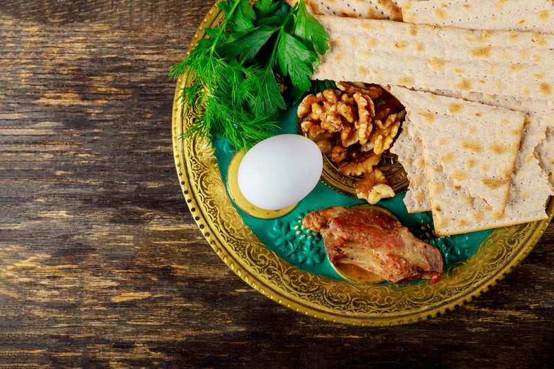 A seder plate sits on a wooden table. Hosting a seder over Zoom can be tricky, but you can still make it a great virtual Passover experiences.