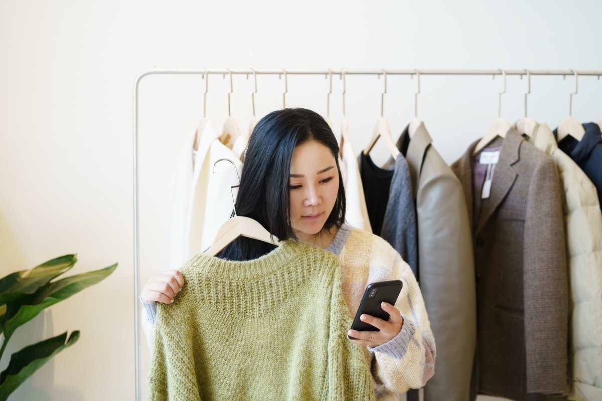 A young woman looks at her phone while holding up a green sweater from her closet that looks like a boutique.