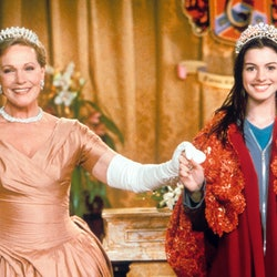 The British actress Julie Andrews, the pseudonym of Julia Elizabeth Wells,wearing a crown and an evening gown, smiles and holds the hand of the young American actress Anne Hathaway in a scene of the film Pretty Princess by Garry Marshall. USA, 2001.. (Photo by Mondadori via Getty Images)
