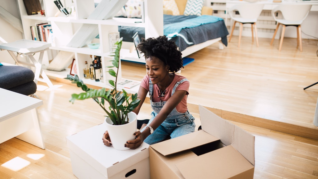 A young woman unpacks a funny planter on Etsy while sitting in her bright apartment.