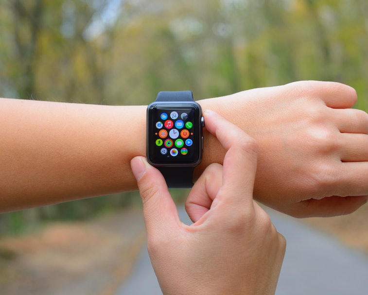 İstanbul, Turkey - November 24, 2015: Hand touching an Apple Watch displaying home screen in a park. Apple Watch is a smart watch, developed by Apple Inc.