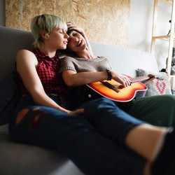 Two young Caucasian women in love sitting on the sofa at home. Spending their time together and relaxing while playing the guitar.