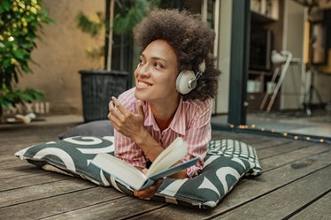 Mixed race woman is relaxing at the home balcony, laying down on the pillows and reading a book