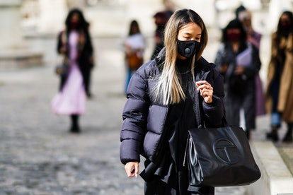 PARIS, FRANCE - OCTOBER 04: A guest wears a face mask with oxygen rechargeable cartridges, a black winter puffer coat, a Telfar black leather bag, a black dress, outside Gabriela Hearst, during Paris Fashion Week - Womenswear Spring Summer 2021, on October 04, 2020 in Paris, France. (Photo by Edward Berthelot/Getty Images)