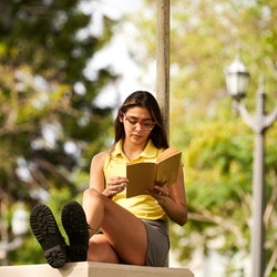 Pretty cheerful casual student girl reading book at the park.