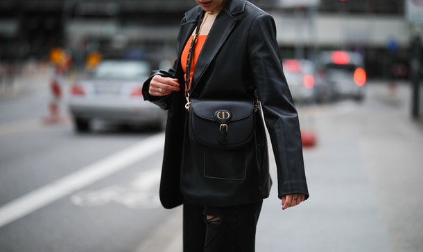 HAMBURG, GERMANY - MARCH 17: Tugba Kement wearing black NA-KD leather blazer, orange Zara top, black pants and boots and black Dior leather Bobby bag on March 17, 2021 in Hamburg, Germany. (Photo by Jeremy Moeller/Getty Images)