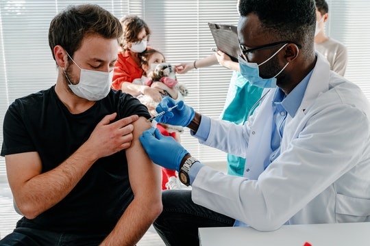 young man  with face mask getting vaccinated, coronavirus, covid-19 and vaccination concept