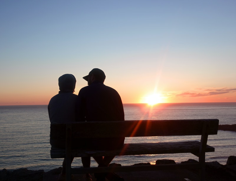 couple watching the sunset on a bench