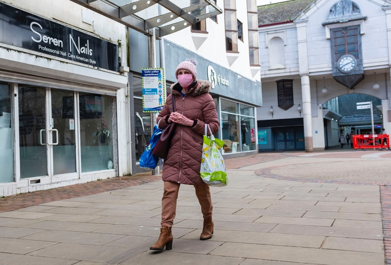 CARMARTHENSHIRE, UNITED KINGDOM - 2021/03/17: A woman wearing a mask as a preventive measure against...