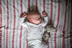 baby sleeping with arms overhead