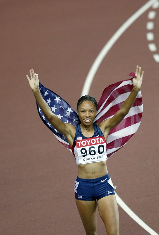 """Allyson Felix holds an American flag behind her as she runs a """"victory lap"""" around a track field."""