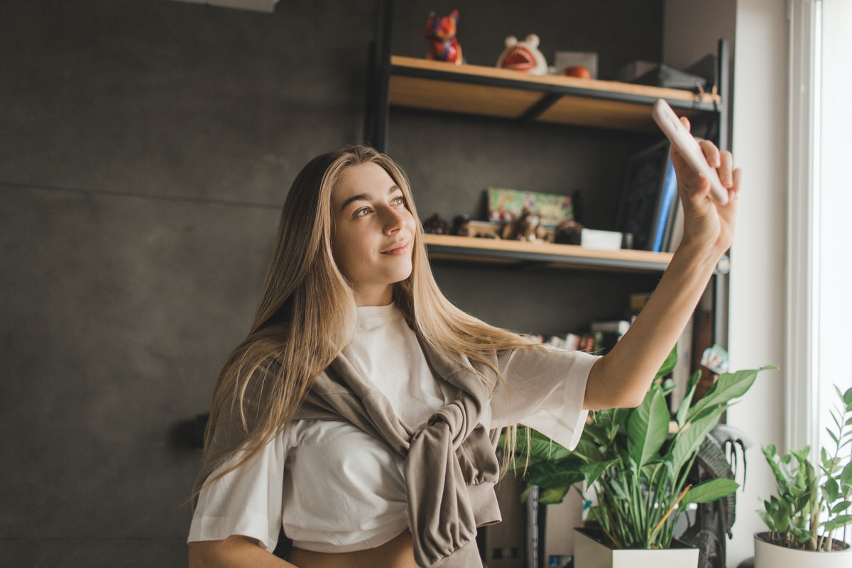 A glowing woman takes a selfie at home, showing off her hair parted in the middle.