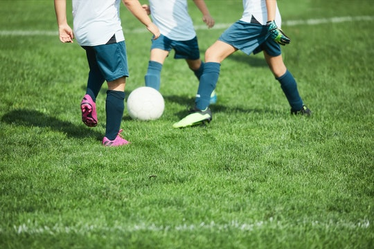 Detail of children's feet on a soccer field with grass on the foreground as copy space.