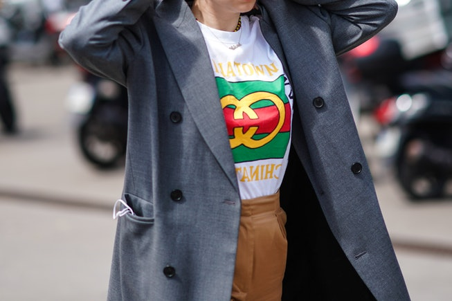 "PARIS, FRANCE - JUNE 19: A guest wears a grey trench coat, a white t-shirt with a colorful logo and the inscription ""Chinatown"", camel pants, outside Acne Studios, during Paris Fashion Week - Menswear Spring/Summer 2020, on June 19, 2019 in Paris, France. (Photo by Edward Berthelot/Getty Images)"