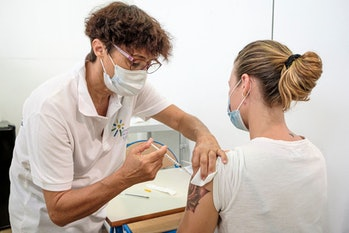 A woman receives a dose of the Pfizer/BioNTech Covid-19 vaccine at a vaccination center setup in the...