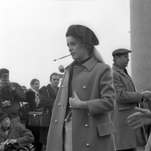French actress Cathrine Deneuve on the set of the movie 'Mayerling', wearing a coat and and a beret, a paintbrush in her mouth with photographer behind her, Venice, March 1968. (Photo by Archivio Cameraphoto Epoche/Getty Images)