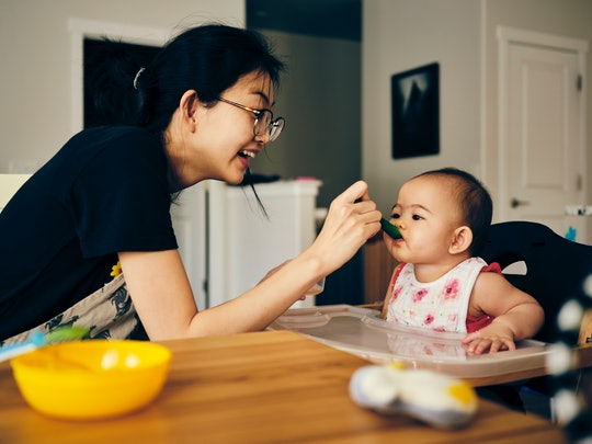 A Japanese mother feeds her 7 month old baby dinner in their home.