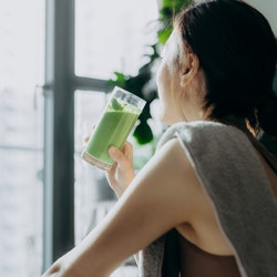 Young Asian sports woman taking a break, refreshing with healthy green juice after fitness work out / exercising / practicing yoga at home in the fresh bright morning